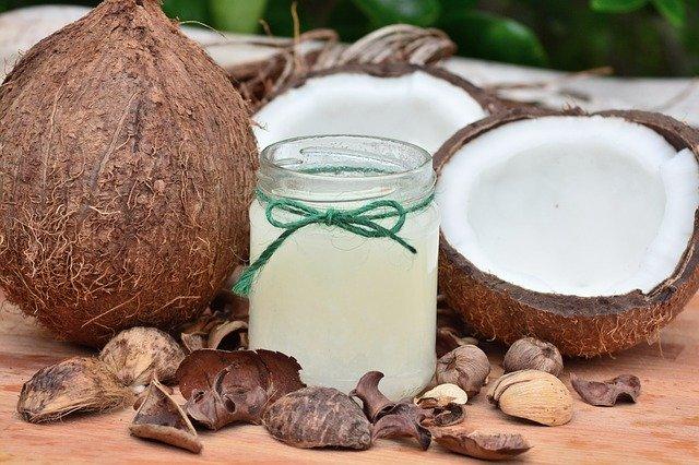 kokosový olej s kokosy v pozadí